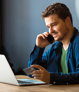 consumer online banking bill pay of man on phone with credit card online on laptop computer