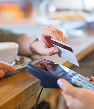 Debit card being used for purchase at coffee shop